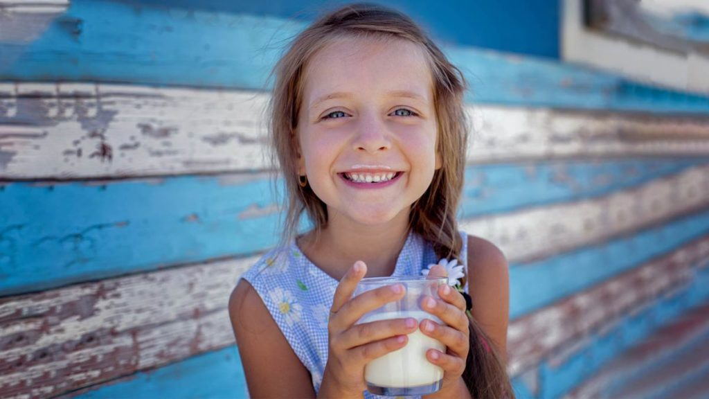 Criança tomando leite por causa da importância do leite